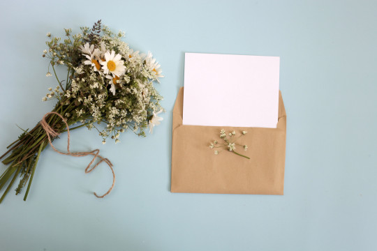 a bunch of flowers and a blank letter