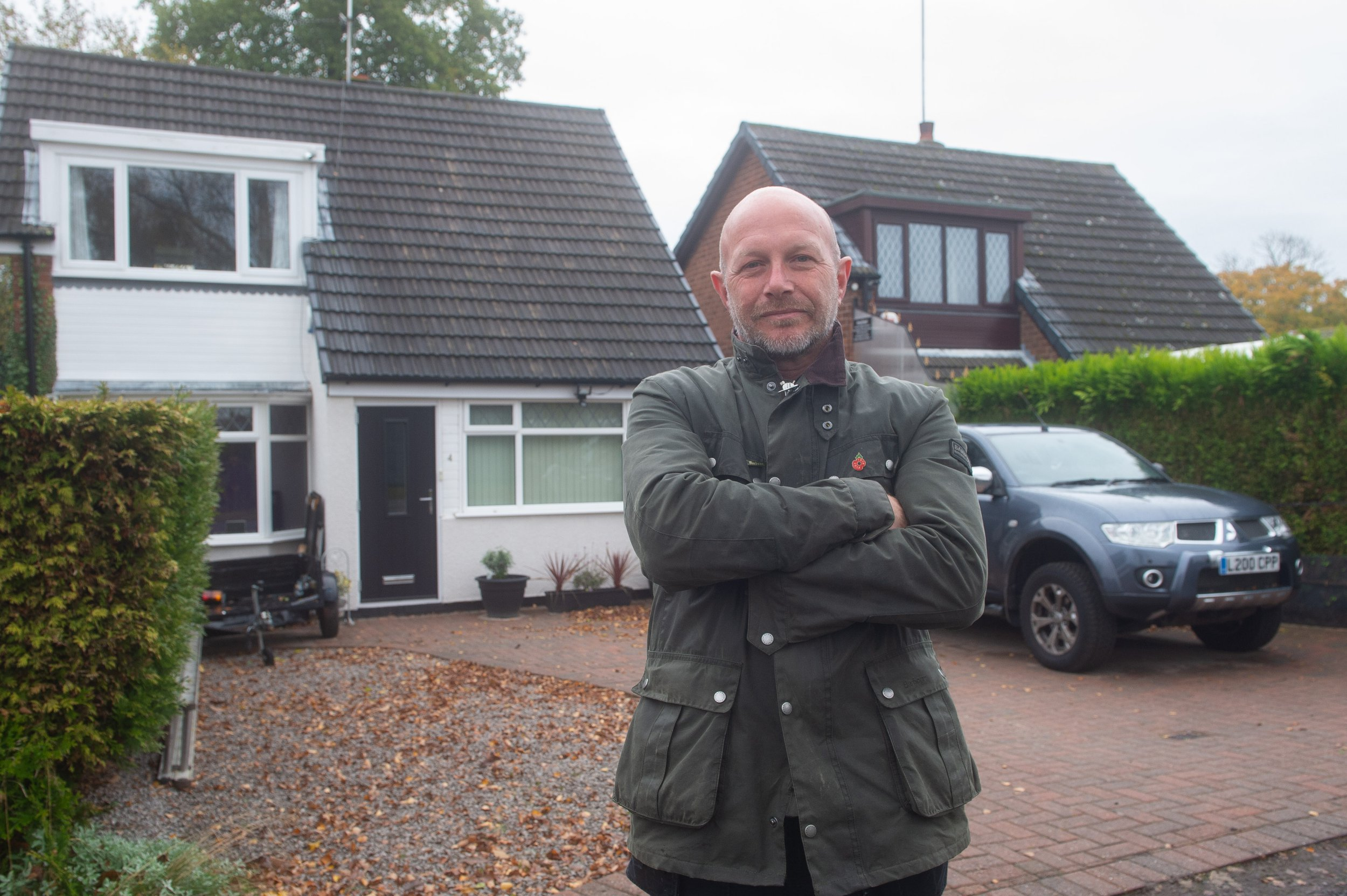Pictured is neighbour Timothy Royle outside his home next door to Michael Hall.