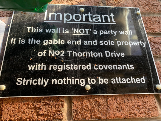 Signs outside Michael Hall's home. Michael Hall a noisy neighbour nicknamed ''Michael the Moron''