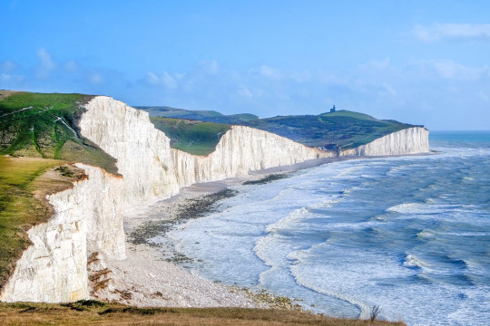Seven Sisters cliffs, tall white chalk cliffs with the sea infront and on top of the cliffs is grass above a blue sky, at the bottom of the nearest cliff is a big pile of chalk from a recent cliff fall of eroded rock,