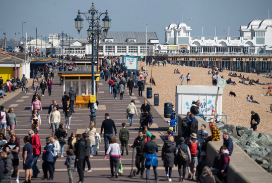 People make their way long the sea front in Southsea, Hampshire, today