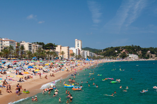 LLORET DE MAR, SPAIN-JULY 8: People swim and sunbathe at the city beach of Lloret de Mar on July 8, 2010 in Lloret de Mar, Spain. The beach is one of the most popular holiday resorts in Spain; Shutterstock ID 60287632; Purchase Order: -