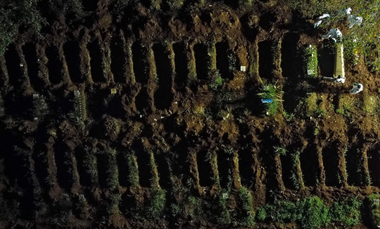 (FILES) This file photo taken on March 31, 2021, shows an aerial view of a coffin being buried at the Vila Formosa cemetery in Sao Paulo, Brazil. - Brazil registered more than 4,000 Covid-19 deaths in 24 hours for the first time on Tuesday, April 6, the health ministry said, as the country reeled from a surge of infections that has made it the current epicenter of the pandemic. (Photo by Miguel SCHINCARIOL / AFP) (Photo by MIGUEL SCHINCARIOL/AFP via Getty Images)