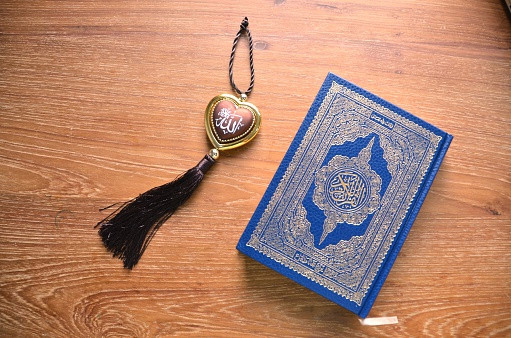 A Qu'ran placed on a table next to a heart shaped keyring.