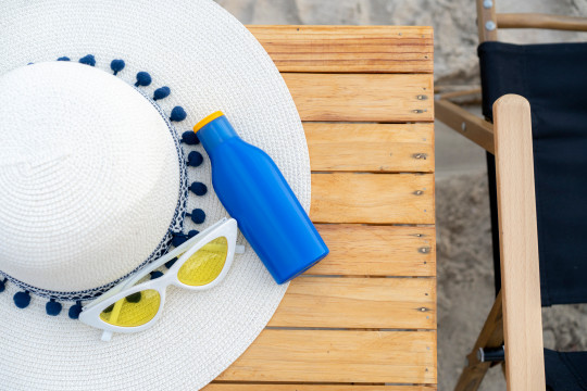 Sunscreen, weave hat and sunglass on wooden table