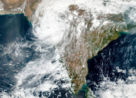 This May, 18, 2021 satellite image released NASA shows Cyclone Tauktae approaching India's western coast. The Indian navy is working to rescue crew members from a sunken barge and a second cargo vessel that was adrift Tuesday off the coast of Mumbai after a deadly cyclone struck the western coast. (NASA Worldview, Earth Observing System Data and Information System (EOSDIS) via AP)