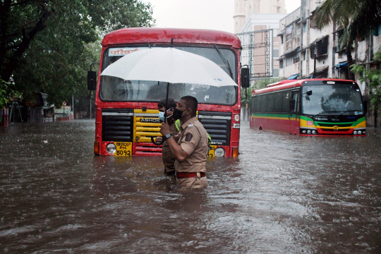 epa09207143 An Indian policeman helps a driver to cross the flooded street as the public transport bus stuck due to heavy rain after cyclone Tauktae hits Mumbai and nearby areas, India, 17 May 2021. According to the India Meteorological Department (IMD) forecast, Cyclone Tauktae will make a landfall over the Gujarat coastal area, including Kerala, Karnataka, Maharashtra and Goa with a wind speed of around 150 kmph. EPA/STR