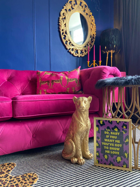 gold leopard statue in living room, by bright pink sofa
