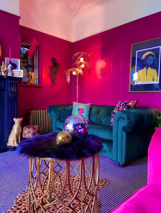 living room after makeover, with pink and teal sofas and leopard print and gold accents