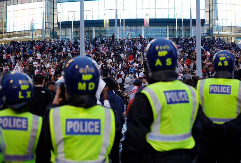 A line of police watch supporters outside Wembley Stadium in London, Sunday, July 11, 2021, during the Euro 2020 final against Italy.