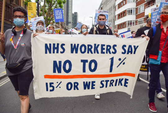 NHS workers marching with a sign that says 'NHS workers say no to 1%, 15% or we strike'. Boris Johnson's government is under intense pressure to announce the pay rise for NHS staff before MPs break up for summer.
