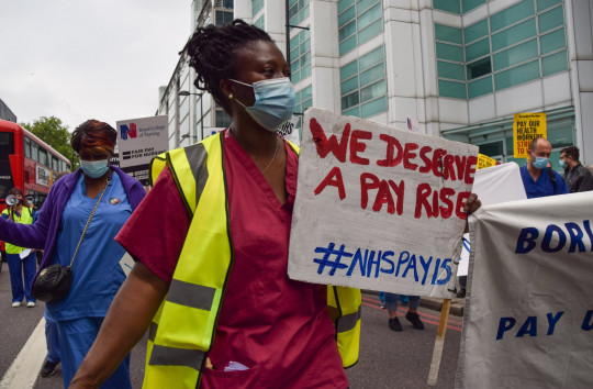 NHS worker holding a sign says 'We deserve a pay rise'. Boris Johnson's government is under intense pressure to announce the pay rise for NHS staff before MPs break up for summer.