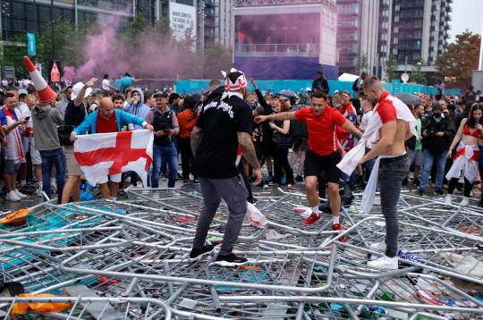 Supporters trample on barricades outside Wembley Stadium in London, Sunday, July 11, 2021, during the Euro 2020 soccer championship final match between England and Italy. (AP Photo/David Cliff)