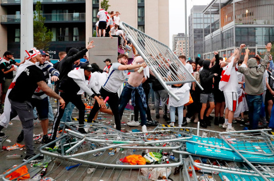Football - Euro 2020 - Final - Fans gather for Italy v England - Wembley Stadium, London, Britain - July 11, 2021 Picture taken July 11, 2021 England fans throw barriers outside Wembley Stadium during the match Action Images via Reuters/Lee Smith