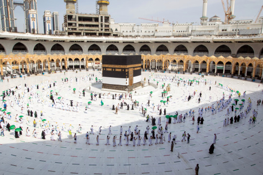 A handout photo made available by the Saudi Ministry of Hajj and Umrah shows Muslim pilgrims, wearing protective face masks, circling around the Kaaba at the Masjidil Haram, Islam's holiest site during the annual Hajj pilgrimage, in the holy city of Mecca, Saudi Arabia, 17 July 2021.