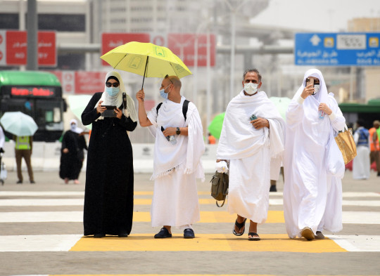 Pilgrims wearing protective face masks walk in the Muslim holy city of Mecca, on the first day of the annual Hajj pilgrimage, Saudi Arabia, 18 July 2021.