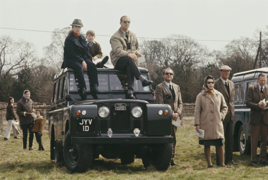 Members of the British royal family, including Queen Elizabeth II standing with Henry Somerset, 10th Duke of Beaufort (1900-1984) beside a Land Rover Series IIA station wagon with Princess Anne, Prince Philip Duke of Edinburgh and Prince Andrew seated on the roof as they observe events at the Badminton horse trials in Gloucestershire, England on 20th April 1969. (Photo by Rolls Press/Popperfoto/Getty Images)